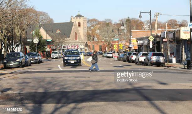 A pedestrian crosses Centre Street in the West Roxbury neighborhood of Boston on Nov 25 2019 The city has proposed reducing the number of lanes on...