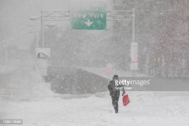 Pedestrian crosses in front of the entrance to I-90 on December 17, 2020 in Boston, Massachusetts. Winter storm Gail is expected to bring more than a...