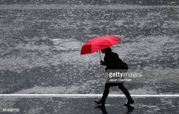 Pedestrian crosses in the intersection of Queen Street and Victoria Street during heavy rain on July 1, 2014 in Auckland, New Zealand. Heavy rain and...