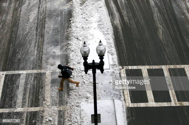 A pedestrian crosses Merrimac Street in Boston during a winter storm on Mar 14 2017