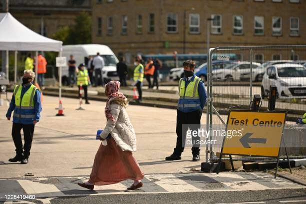 Pedestrian crosses the road at an NHS COVID-19 drive-in testing centre in Bolton, northern England on September 9 as local lockdown restrictions are...