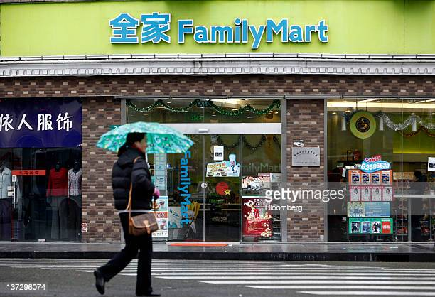 A pedestrian crosses the road in front of a FamilyMart Co convenience store in Shanghai China on Sunday Jan 15 2012 FamilyMart Co Japan's largest...