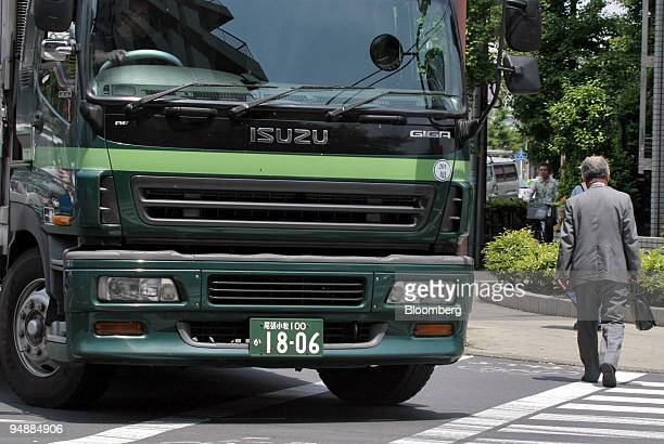 A pedestrian crosses the road in front of an Isuzu Motors Giga commercial truck in Tokyo Monday May 23 2005 Isuzu Motors Ltd Japan's biggest maker of...