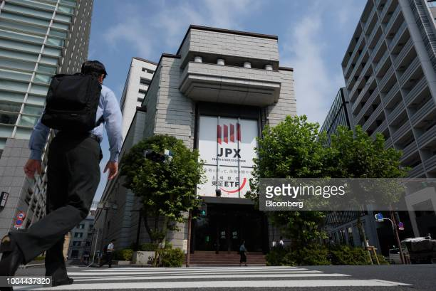 A pedestrian crosses the road in front of the Tokyo Stock Exchange operated by Japan Exchange Group Inc in Tokyo Japan on Tuesday July 24 2018...