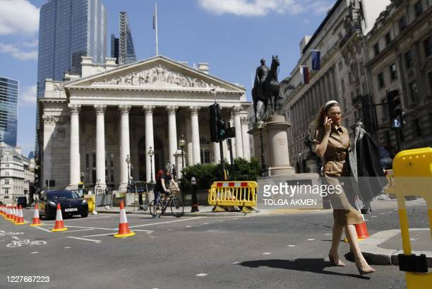 A pedestrian crosses the road near the Royal Exchange and the Bank of England in the City of London on July 17 2020 Boris Johnson said on July 17 he...