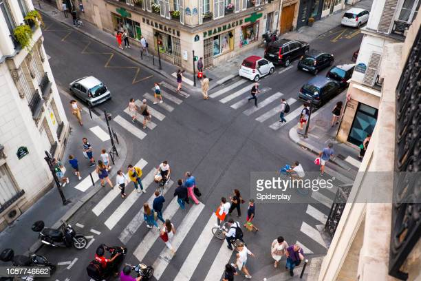 pedestrian crossing at street intersection in paris - road junction stock pictures, royalty-free photos & images