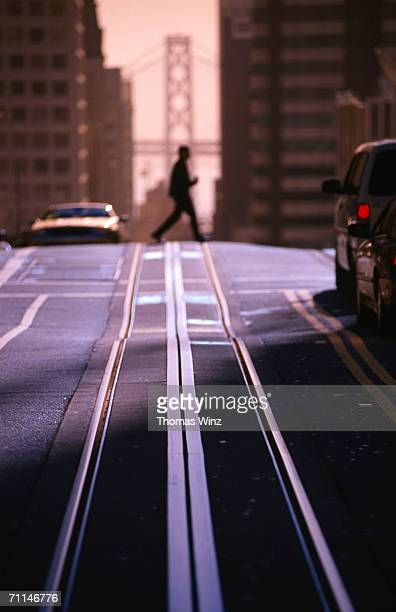 Pedestrian crossing cable car tracks on Nob Hill with Bay Bridge in background, San Francisco, United States of America