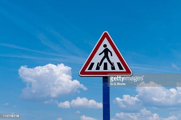 Pedestrian crossing road sign between clouds
