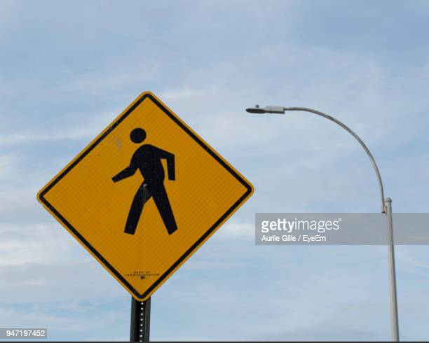 pedestrian crossing sign against sky - pedestrian crossing sign stock photos and pictures