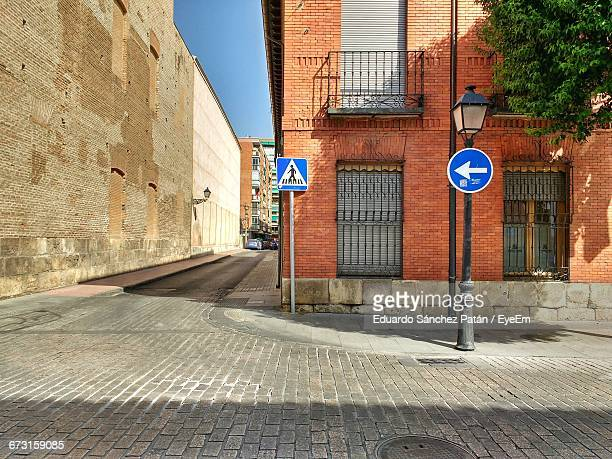pedestrian crossing sign and directional sign on footpath by building - alcala de henares stock pictures, royalty-free photos & images