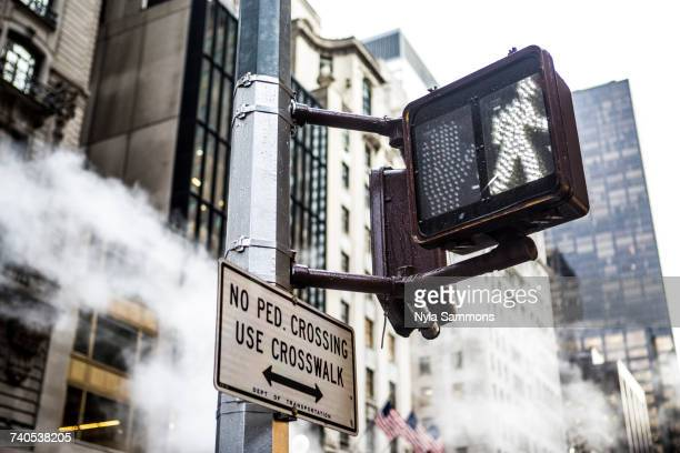 pedestrian crossing sign and skyscrapers, new york city, usa - pedestrian crossing sign stock photos and pictures