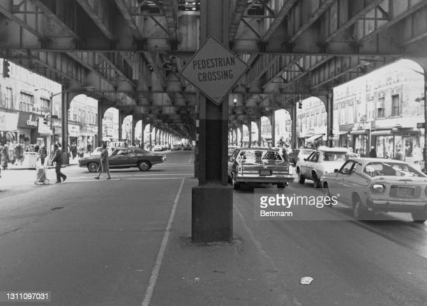 Pedestrian crossing sign fixed to a vertical support as traffic passes beneath an elevated rail line in the Brighton Beach neighbourhood in the...