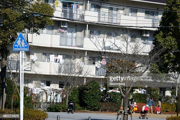 A pedestrian crossing sign stands as mothers and children play in a park in front of a residential building in Inzai Chiba Prefecture Japan on...