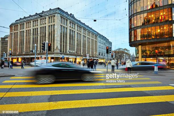 pedestrian crossing with electric car on the corner of bahnhofstrasse and uraniastrasse, zurich, switzerland - チューリッヒ ストックフォトと画像
