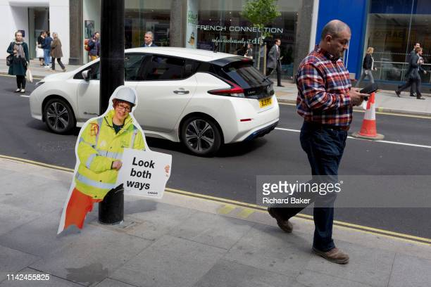A pedestrian distracted with his mobile phone walks past a broken warning construction work figure one of many up and down both sides of the...