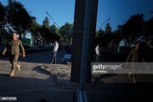 A pedestrian dressed in military uniform is reflected in the window of a store in Dushanbe Tajikistan on Saturday April 21 2018 Flung into...