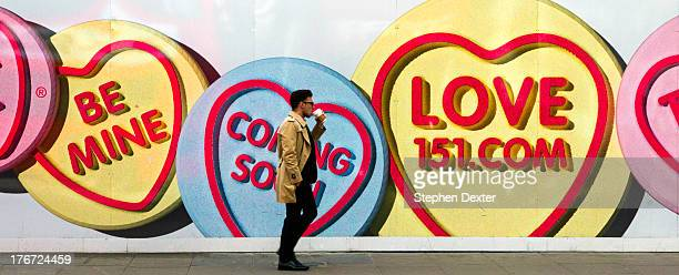 Pedestrian drinking coffee as he walks past an advertising billboard on the side of a construction site. Oxford Street in Westminster London.