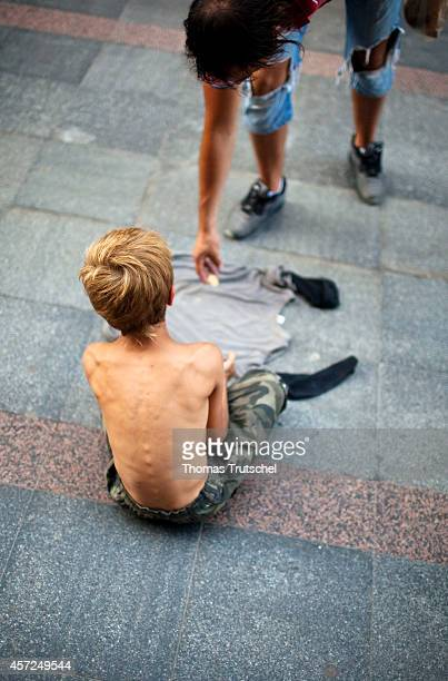Pedestrian giving money to a begging boy on August 06 in Sarajevo Bosnia and Herzegovina
