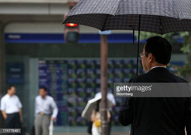 A pedestrian holding an umbrella waits to cross a road in front of an electronic stock board outside a securities firm in Tokyo Japan on Monday July...