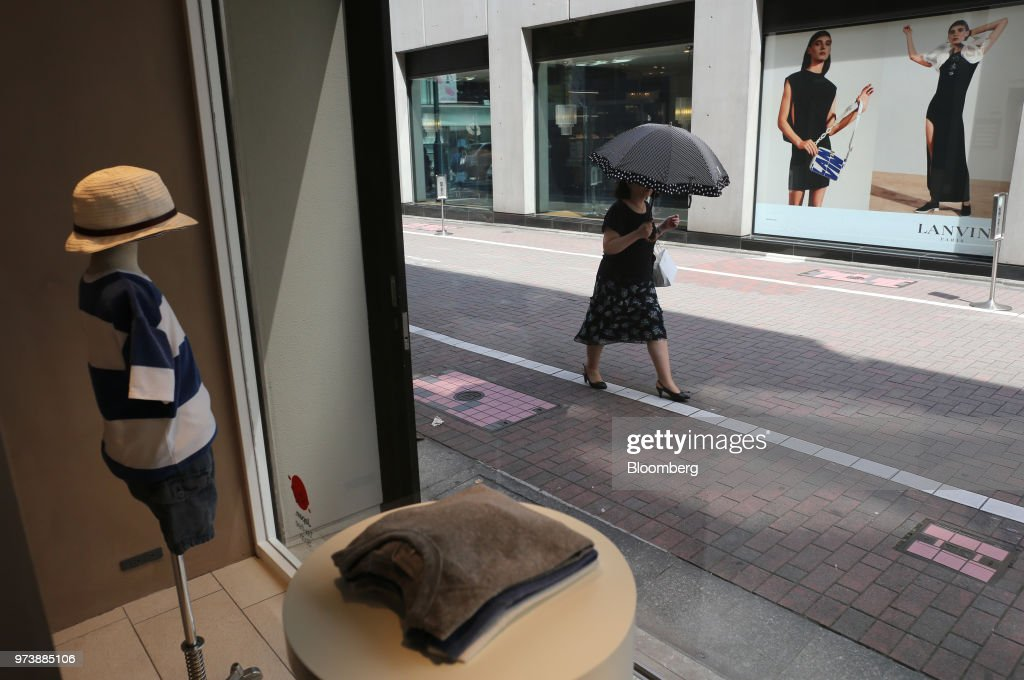 A pedestrian holding an umbrella walks past a display at a Sayegusa Inc. children's clothing store in the Ginza district of Tokyo, Japan, on Sunday, May 28, 2018. The savings-rich elderly spend about 9.7 trillion yen ($87 billion) a year on their offspring and such spending last year accounted for about a third of the modest growth in total consumption, according to Hiromichi Shirakawa, chief Japan economist at Credit Suisse Group. Photographer: Takaaki Iwabu/Bloomberg via Getty Images