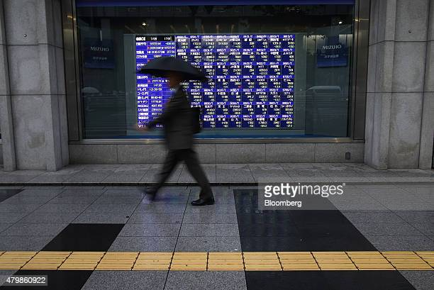 A pedestrian holding an umbrella walks past an electronic stock board outside a securities firm in Tokyo Japan on Wednesday July 8 2015 Japanese...