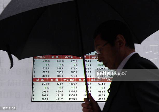 Pedestrian holding an umbrella walks past an electronic stock board outside a securities firm in Tokyo, Japan, on Wednesday, April 28, 2010. Japanese...