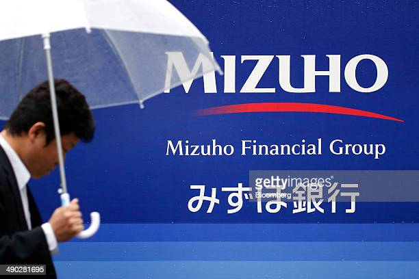 A pedestrian holding an umbrella walks past the corporate logo of Mizuho Financial Group Inc displayed outside a Mizuho Bank Ltd branch in Tokyo...