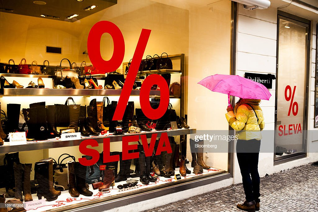 A pedestrian holds an umbrella as she looks in the window of a shoe store offering sale prices in Prague, Czech Republic, on Tuesday, Jan. 8, 2013. The Czech economy is showing weak domestic demand as households and businesses cut spending due to government austerity programs and the euro area's debt crisis. Photographer: Bartek Sadowski/Bloomberg via Getty Images