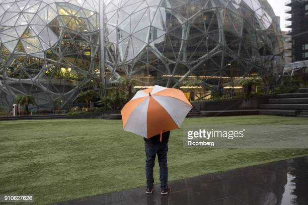 A pedestrian holds an umbrella while standing in front of the Amazoncom Inc Spheres in Seattle Washington US on Tuesday Jan 23 2018 The online...