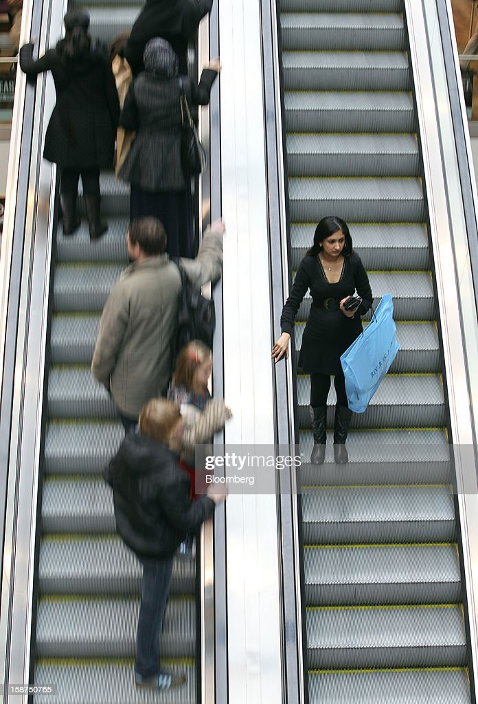 A pedestrian holds her goods in a shopping bag as she travels on an escalator at the Westfield Stratford City shopping mall in London, U.K., on Thursday, Dec. 27, 2012. Overall Christmas shopping in the U.K. was similar to last year, according to the British Retail Consortium. Photographer: Chris Ratcliffe/Bloomberg via Getty Images