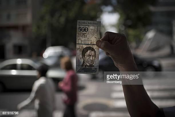 A pedestrian holds up a new 500 Bolivar banknote for a photograph in Caracas Venezuela on Tuesday Jan 17 2017 Since Venezuela's President Nicolas...