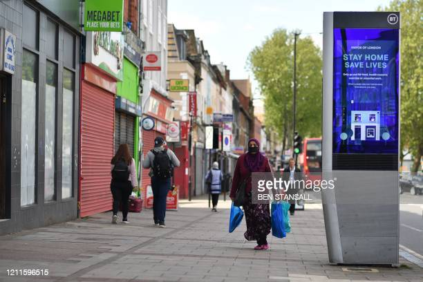 Pedestrian in a face mask walks in a street where an electronic billboard urges the public to stay at home in the London borough of Newham, east...