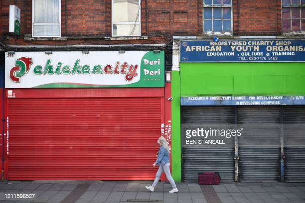 Pedestrian in a face mask walks past closed shops in the London borough of Newham, east London, on May 2 as life in Britain continues during the...