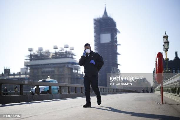 A pedestrian in a mask walk along Westminster Bridge with Elizabeth Tower in the backgroud in a quiet central London on March 25 after Britain's...