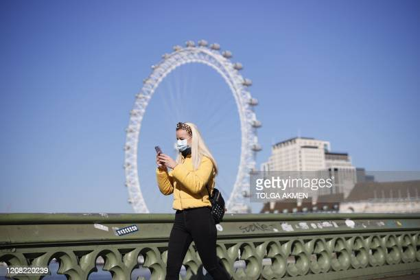 A pedestrian in a mask walks along Westminster Bridge with the London Eye in the backgroud in a quiet central London on March 25 after Britain's...