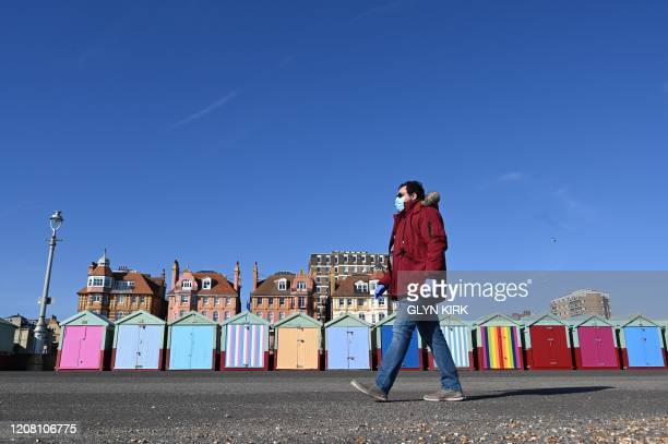TOPSHOT A pedestrian in a mask walks past the beach huts on the sea front at Hove Brighton southern England on March 24 2020 after Britain ordered a...