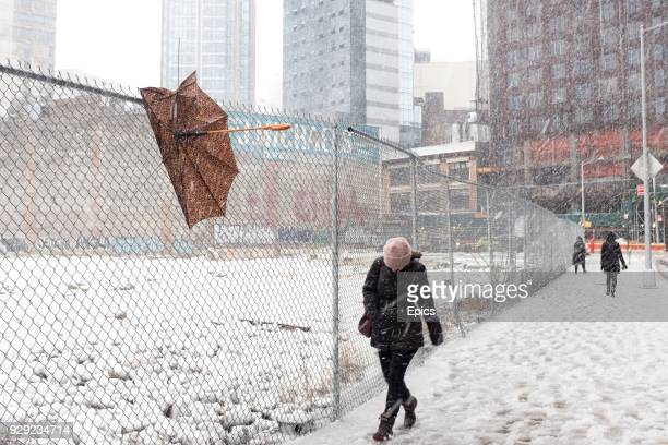 A pedestrian in downtown Brooklyn passes by a broken umbrella as they battle the heavy wet snow as winter storm Quinn hits New York and the Northeast