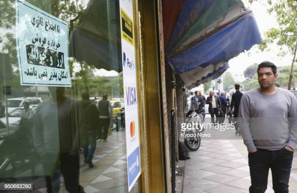 A pedestrian in this photo taken on April 17 looks at a sign that reads 'We don't buy or sell foreign currencies' at an exchange office in Tehran as...