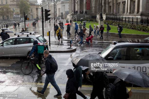 A pedestrian is picked up after falling over in the road during autumnal downpour in Trafalgar Square in central London on 1st October 2019 in London...