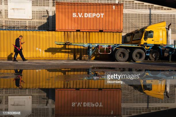 A pedestrian is reflected in a puddle of water while walking past trailers and shipping containers at the site of a former depot in Bangkok Thailand...