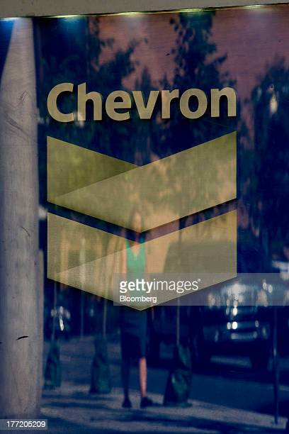 A pedestrian is reflected in a window and the logo for Chevron Corp at Chevron Plaza in Calgary Alberta Canada on Wednesday Aug 14 2013 Statistics...
