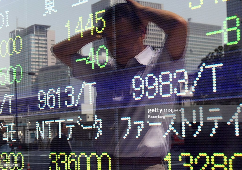 A pedestrian is reflected in an electronic stock board outside a securities firm in Tokyo, Japan, on Friday, May 21, 2010. Japanese stocks fell, putting key indexes on course for their biggest weekly drops in more than a year, as rising U.S. unemployment and a deepening split in Europe spurred concern the global economic recovery will stall. Photographer: Tomohiro Ohsumi/Bloomberg via Getty Images