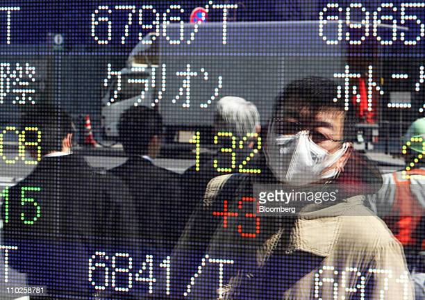 A pedestrian is reflected in an electronic stock board outside a securities firm in Tokyo Japan on Thursday March 17 2011 Japanese equities reversed...