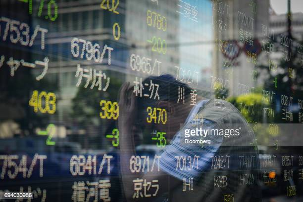 A pedestrian is reflected in an electronic stock board outside a securities firm in Tokyo Japan on Friday June 9 2017 The Topix index closed higher...