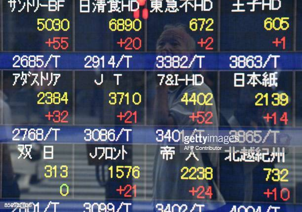 A pedestrian is reflected in the window of a securities company showing stock prices on the Tokyo Stock Exchange in Tokyo on October 3 2017 Tokyo's...