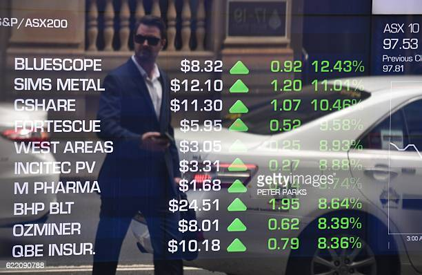 A pedestrian is reflected in the window of the Australian Securities Exchange showing stocks gains during opening trading in Sydney on November 10...