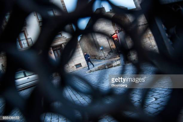 A pedestrian is seen through a fence in the Old City of Baku Azerbaijan on Friday March 16 2018 Azerbaijan's economy barely returned to growth last...