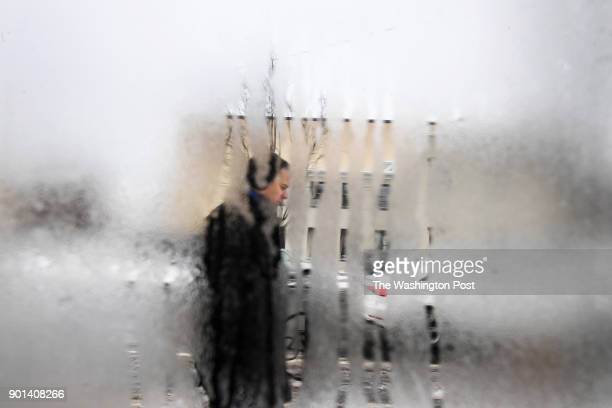 A pedestrian is seen through a window covered in condensation as a storm hit the area on Thursday January 04 2018 in Alexandria VA