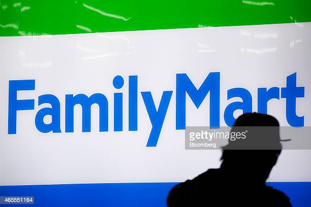 A pedestrian is silhouetted against the illuminated signage for FamilyMart Co outside one of the company's stores in Tokyo Japan on Saturday March 7...