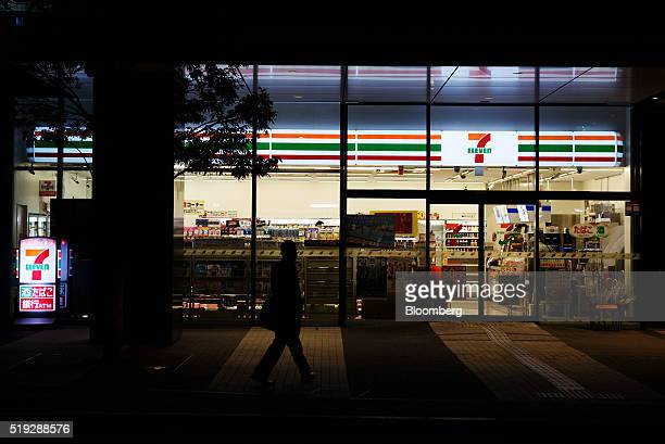 A pedestrian is silhouetted as he walks past a 7eleven convenience store operated by Seven i Holdings Co at night in Kawasaki City Kanagawa...